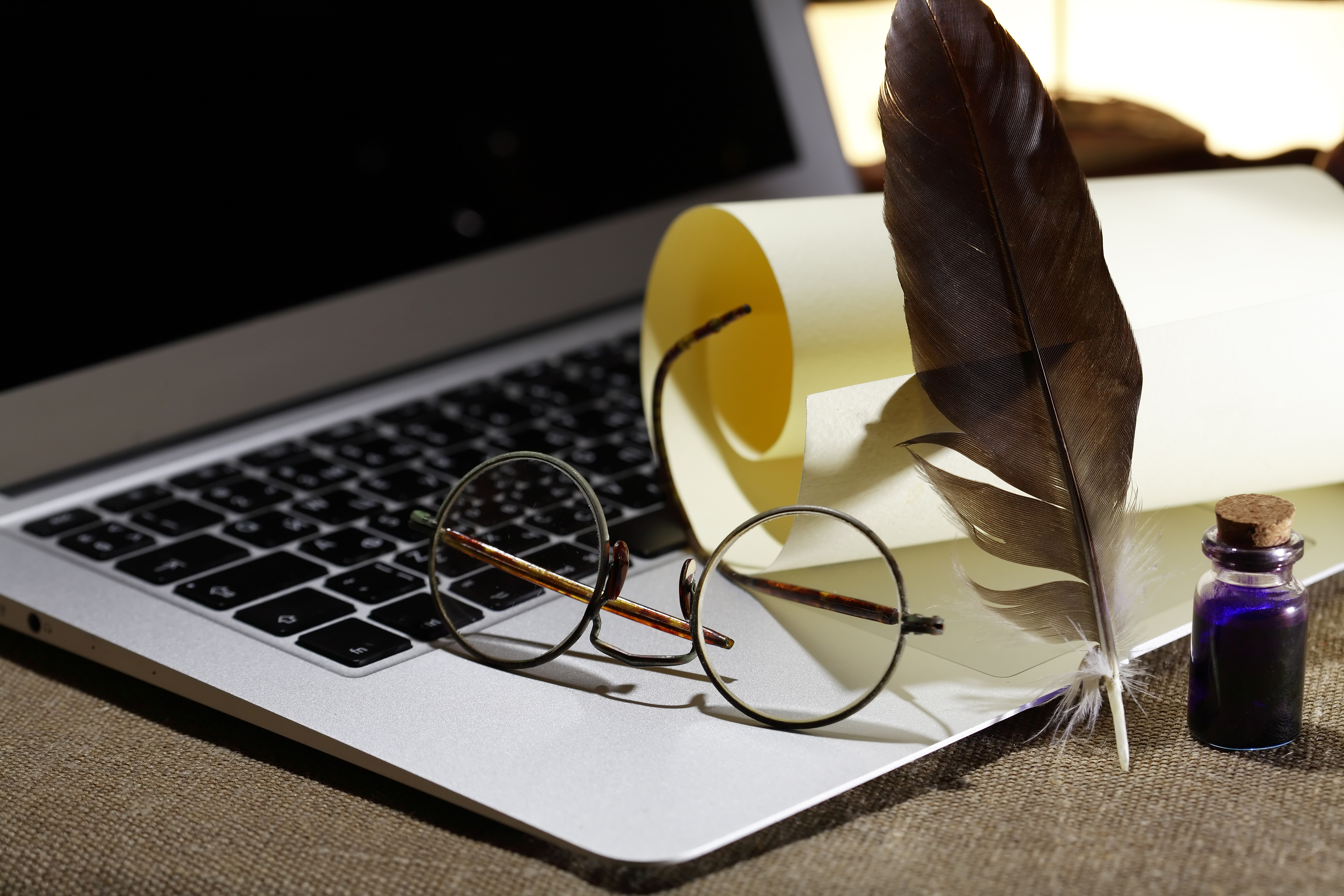 Modern literature. Still life with scroll and quill on modern laptop